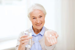 Happy senior woman with water and medicine at home Stock Images