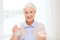 Happy senior woman with water and medicine at home Royalty Free Stock Photos