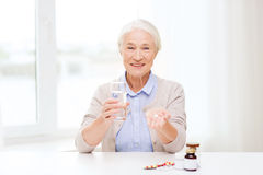 Happy senior woman with water and medicine at home Royalty Free Stock Photo