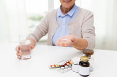 Happy senior woman with water and pills at home Royalty Free Stock Photo