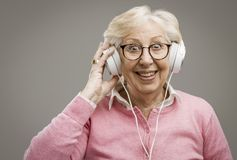 Happy senior woman wearing headphones. And listening to some good music, she is cheerful and enjoying royalty free stock photography
