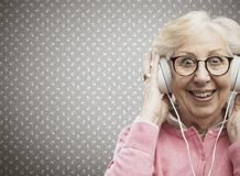 Happy senior woman wearing headphones stock images