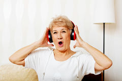 Happy senior woman wearing red headphones Stock Photos