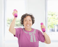 Happy senior woman working out with dumbbells Royalty Free Stock Images