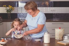 Grandmother and granddaughter cook Stock Photos