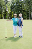 Happy senior women golfing. Two elderly women having fun during a round of golf on the putting green stock images