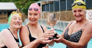 Happy senior women holding trophy. Portrait of happy senior women holding trophy stock video footage