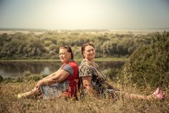 Couple senior women sisters resting together back to back in countryside in sunny summer day. Happy senior women sisters resting together back to back in Stock Photography