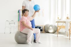 Senior woman using blue ball. Happy senior women sitting on grey ball and exercising in clinic using a blue ball Royalty Free Stock Photos