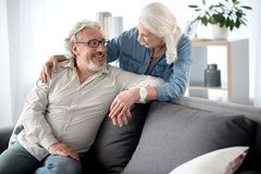 Glad mature married couple enjoying time together. Happy senior women is standing and embracing her husband while holding his hand. Man is sitting on couch and Royalty Free Stock Images