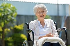 Happy senior women in wheelchair. Happy senior woman sitting on wheelchair and recovering from illness. Handicapped mature woman sitting in wheelchair smiling stock images