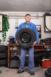 Happy senior worker changing tire in garage. Portrait of happy senior worker changing tire in the garage Stock Images