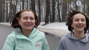 Happy Senior and young Caucasian women running in the snowy park in winter talking and smiling. Close up front follow shot.  stock footage