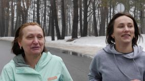 Happy Senior and young Caucasian women running in the snowy park in winter talking and smiling. Close up front follow shot. Slow M. Otion stock video