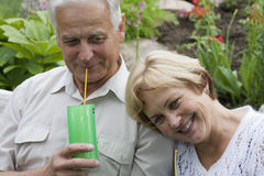Happy seniors - 42 years in love. Senior couple drinking cocktailes in a blossoming garden royalty free stock photo