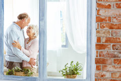 Seniors looking at each other. Happy seniors in apartment looking at each other with love Stock Image