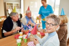 Happy seniors on a birthday party. Happy seniors at a birthday party in retirement home at the coffee table royalty free stock photos