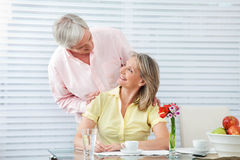 Happy seniors at breakfast. Two happy seniors smiling at breakfast table Royalty Free Stock Image