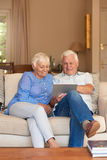 Happy seniors browsing the internet from their living room sofa. Content senior couple talking and relaxing together while sitting on a sofa in their living room Royalty Free Stock Photos