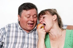 Happy seniors couple with apple Stock Photo