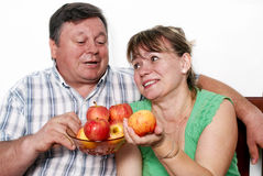Happy seniors couple with apple Stock Images