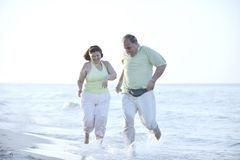 Happy seniors couple  on beach. Happy senior mature elderly people couple have romantic time on beach at sunset Stock Image