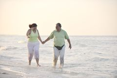 Happy seniors couple on beach. Happy senior mature elderly people couple have romantic time on beach at sunset Royalty Free Stock Photo