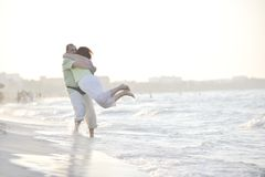 Happy seniors couple  on beach. Happy senior mature elderly people couple have romantic time on beach at sunset Royalty Free Stock Image