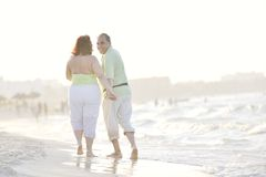 Happy seniors couple  on beach. Happy senior mature elderly people couple have romantic time on beach at sunset Royalty Free Stock Images