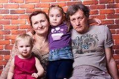 Happy seniors couple with grandchildren Stock Images