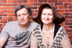 Happy seniors couple in love. Against brick wall stock image