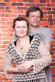 Happy seniors couple in love. Against brick wall stock photos