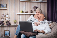 Happy seniors couple reading from laptop in cozy room; Royalty Free Stock Photos