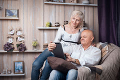 Happy seniors couple reading from tablet in cozy room; Stock Photography