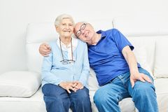 Happy seniors couple is sitting on the sofa. At home or in a retirement home stock image