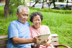 Happy seniors couple with tablet pc Royalty Free Stock Photography