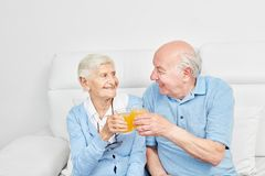Happy seniors couple toasting with orange juice. At home or in retirement home stock images