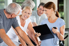 Happy seniors with fitness trainer. In a gym Royalty Free Stock Photos