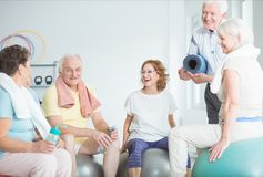 Happy seniors on gym balls. Happy seniors sitting on gym balls at a fitness studio and talking after a successful workout session stock image