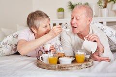 Happy seniors having breakfast in bed. Together in romanctic pension stock photo