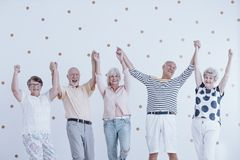Happy seniors jumping. Group of happy seniors holding hands and jumping in the air royalty free stock photo