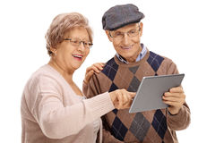 Happy seniors looking at a tablet Stock Photography