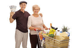 Happy seniors with money bundles and shopping cart full of groce Royalty Free Stock Photo