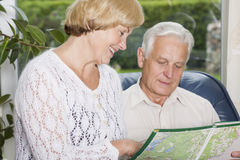 Happy seniors planning a trip. Senior couple home looking into a map royalty free stock image