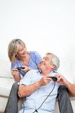 Happy seniors playing computer. Two happy seniors playing computer games with game controller Stock Photography