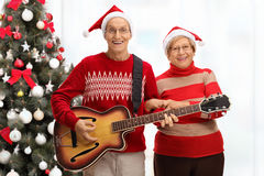 Happy seniors playing a guitar in front of a Christmas tree. Happy seniors playing a guitar in front of Christmas tree royalty free stock photography