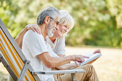 Happy seniors reading a book. Together in the nature in summer royalty free stock photo