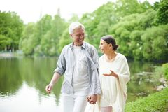 Taking pleasure in walk. Happy seniors taking walk along waterside and talking about some pleasant things royalty free stock photos