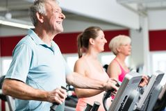 Seniors train on cross trainer with personal trainer at the gym Stock Image