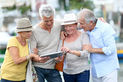 Happy seniors travelling and visiting using tablet. Senior tourists using tablet on visiting journey Stock Photo